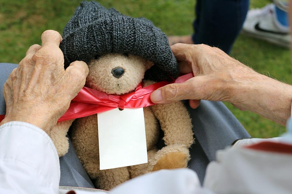 mani di un anziano tengono orsetto con fiocco